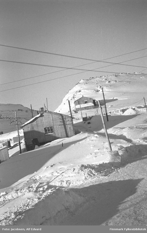 En snødekt del av Havøysund. To ganske store bygninger og flere små står på området. Det nærmeste har stående panel og et sprossevindu på røstveggen. En skorstein ses på taket og noen esker/kasser står inntil veggen. Dette kan være Televerkets bygg der Fridtjof Jacobsen jobbet fram til 1947. Ved foten av den lille knausen står et bygg til. Det har også stående panel og et to-delt vindu på røstveggen. En skorstein ses på taket og et lite tilbygg i enden, som er like langt som røstveggen, har noe snø på taket. Mellom de to byggene står en grunnmur delvis dekket av snø. Flere små bygninger står helt til venstre på bildet. De kan ha noe med el-forsyningen til Havøysund å gjøre. Mange stolper står spedt rundt på området, flere av dem med tilhørende ledninger. Noen ledninger går på kryss og tvers oppe på bildet.