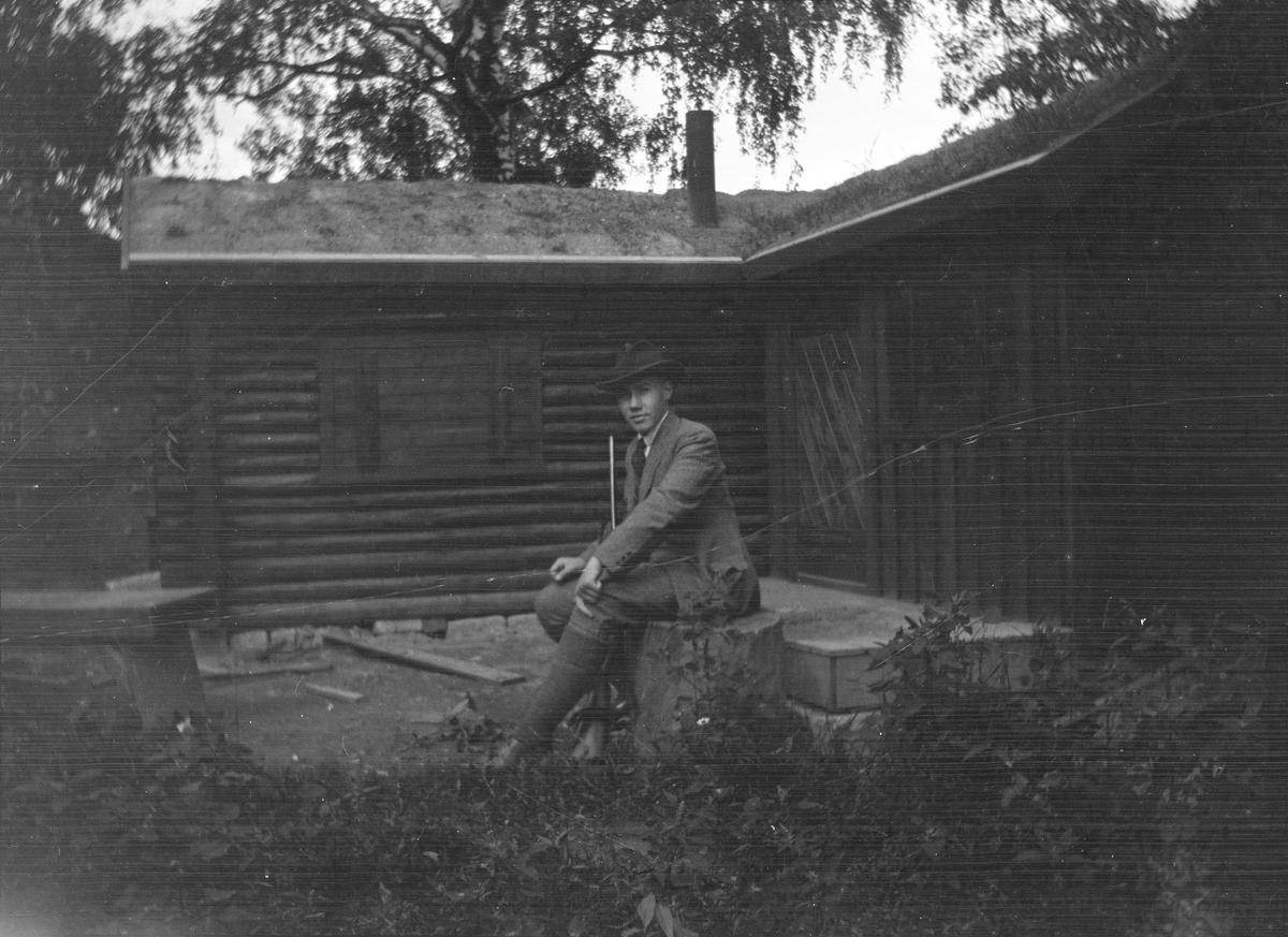 Iacob Ihlen Mathiesen sitter på en stor stubbe utenfor en tømmerhytte med torvtak. På bakken, mellom bena, står et jaktgevær.