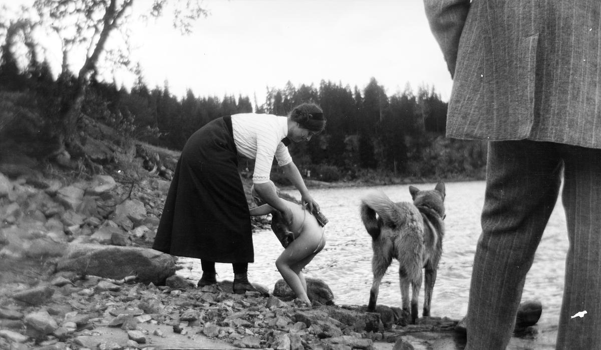 En kvinne hjelper et barn med håndkle og tørking etter et bad i innsjøen. En elghund står ved siden av dem i strandkanten. Foran står en mann med ryggen til kameraet. Bildet er kanskje tatt i Jeppedalen.