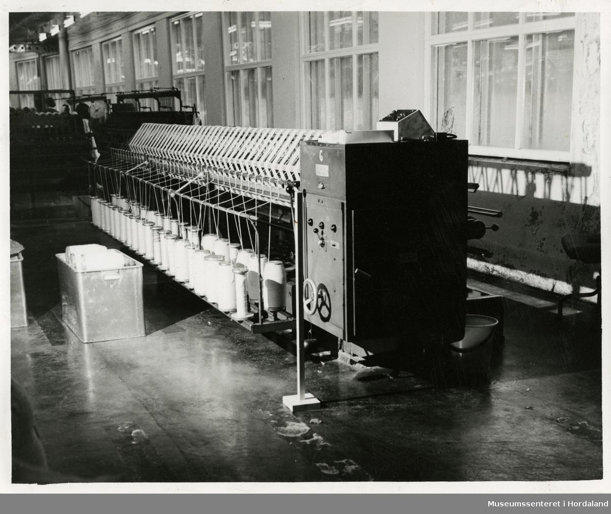 Hespebom i produksjonslokala til Dale Fabrikker. Maskina overfører garn frå trekoner til hesper.