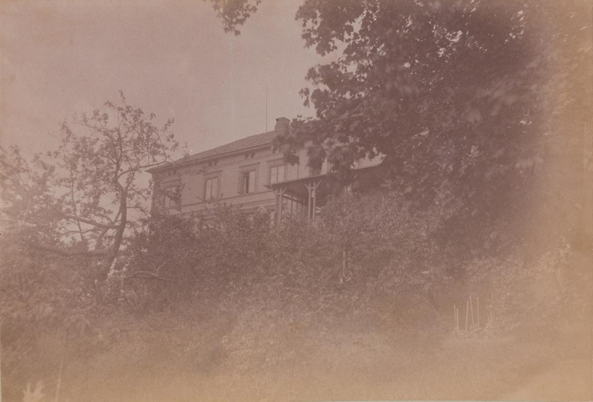 Linderud Gård hovedhus sett fra baksiden, og hagen med frukttrær.