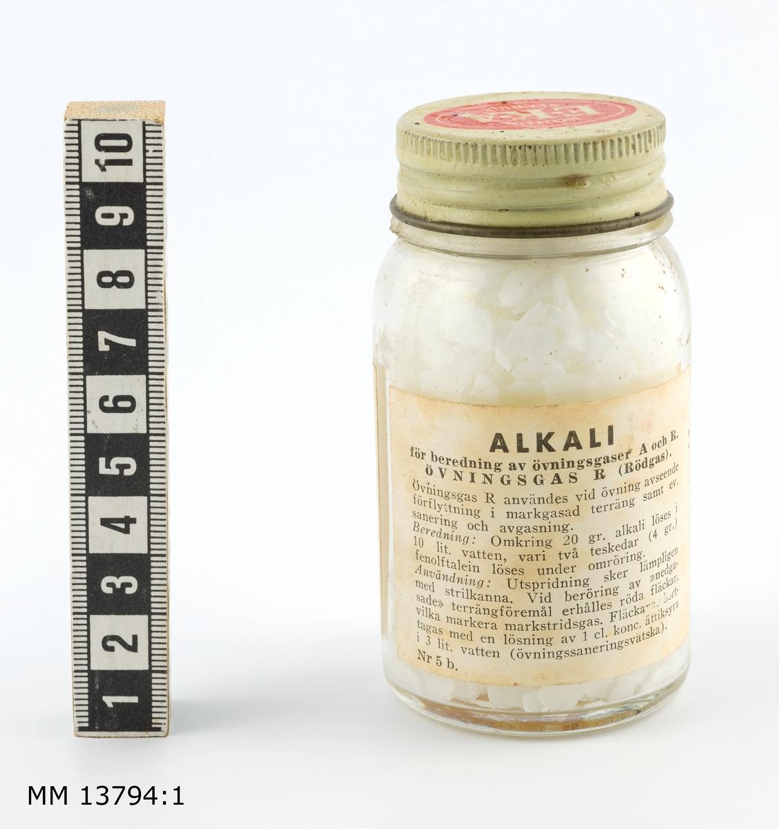 Alkalilösning för beredning av övningsgas. Förvaras i glasburk med skruvlock. På burken etikett med bruksanvisning.