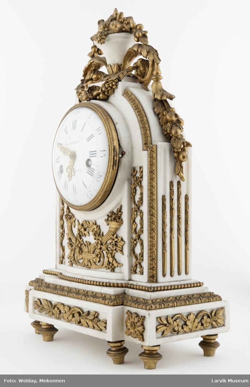 Form: 5små dreide messingben under marmorfot. øverst vase av marmor, hvorfra det faller blomsterranker av messing. hele uret dekket av blomsterdekor i messing.
