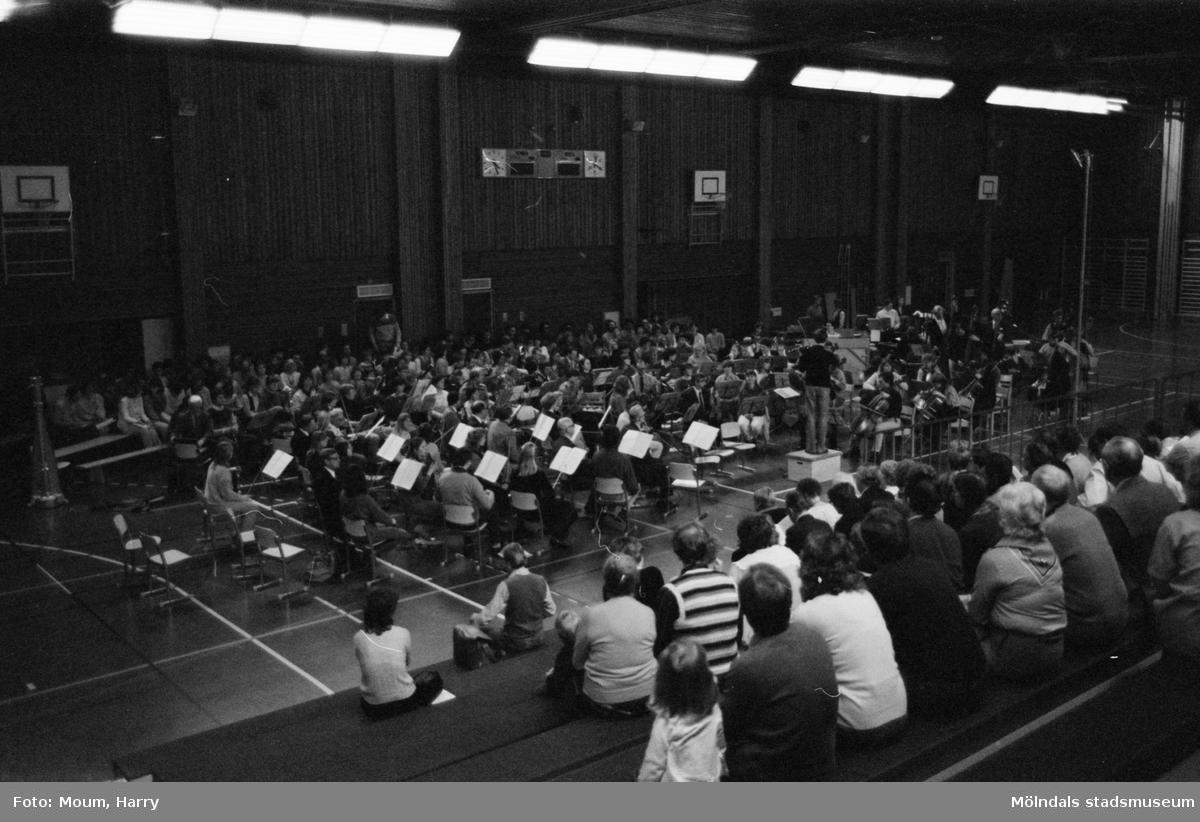 240 medverkande från Chalmers manskör, Collegium Musicum, Mölndals körsällskap, Mölndals vokalensemble, barnkör från Brattåsskolan, Göteborgs Ungdomssymfoniker, Mölndals Musiksällskap samt solister från Storan håller konsert på Ekenskolan i Kållered, år 1984.  För mer information om bilden se under tilläggsinformation.