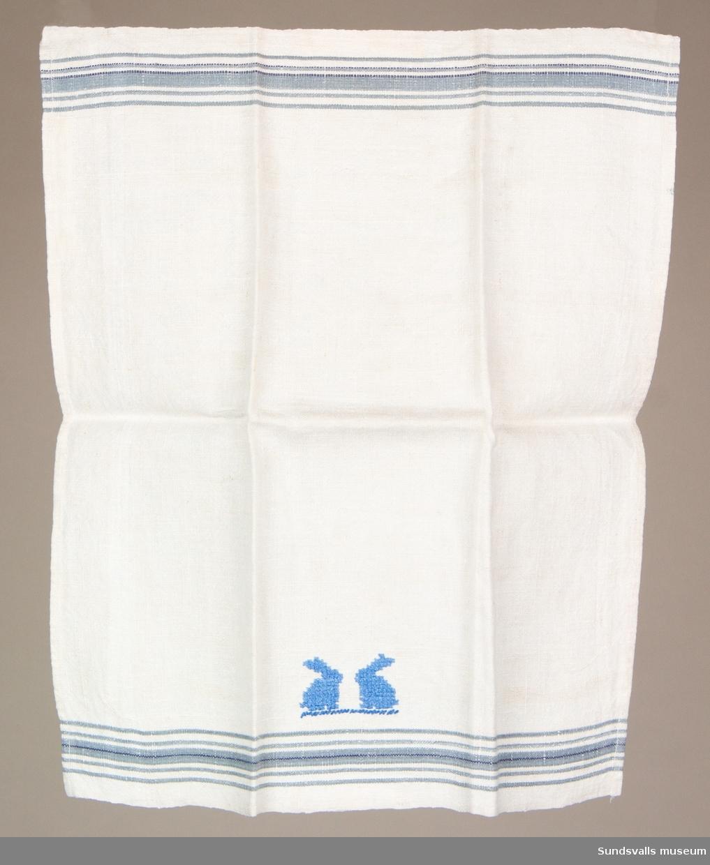 Barnhandduk i linne med ljusblå korsstygnsbroderier föreställande två kaniner.