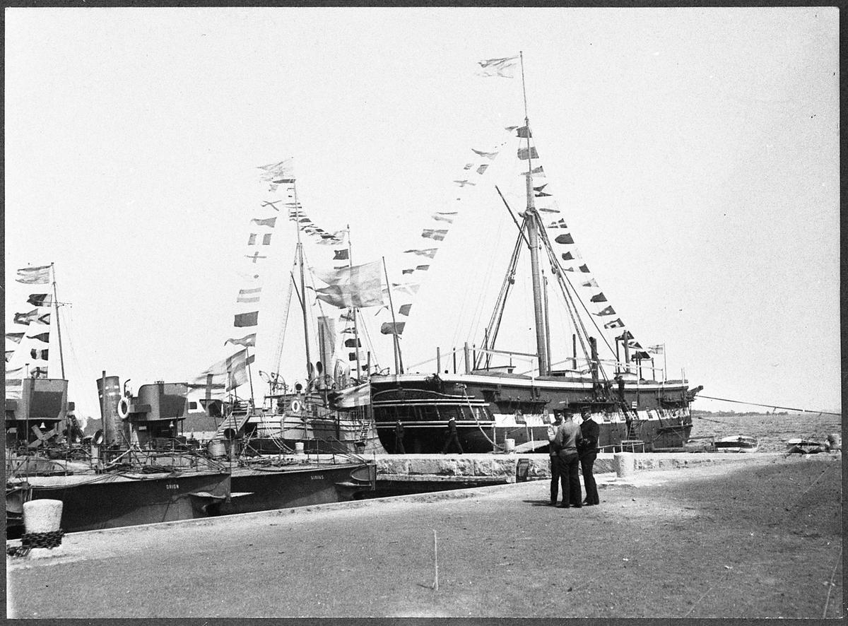 Huvudmotiv är korvetten af Chapman som ligger förtöjt vid en kaj. Fartyget är nedriggad och ombyggd till logementsfartyg. Bredvid på babordssidan ligger kanonbåt Blenda. På bildens vänster sida ser man förstävar av 1. klass torpedbåtar Orion och Sirius. Alla båtar är flaggad. I föregrunden står en grupp av tre men som samtalar.  Bilden ska framställa Torpedskolan på Almö år 1907.