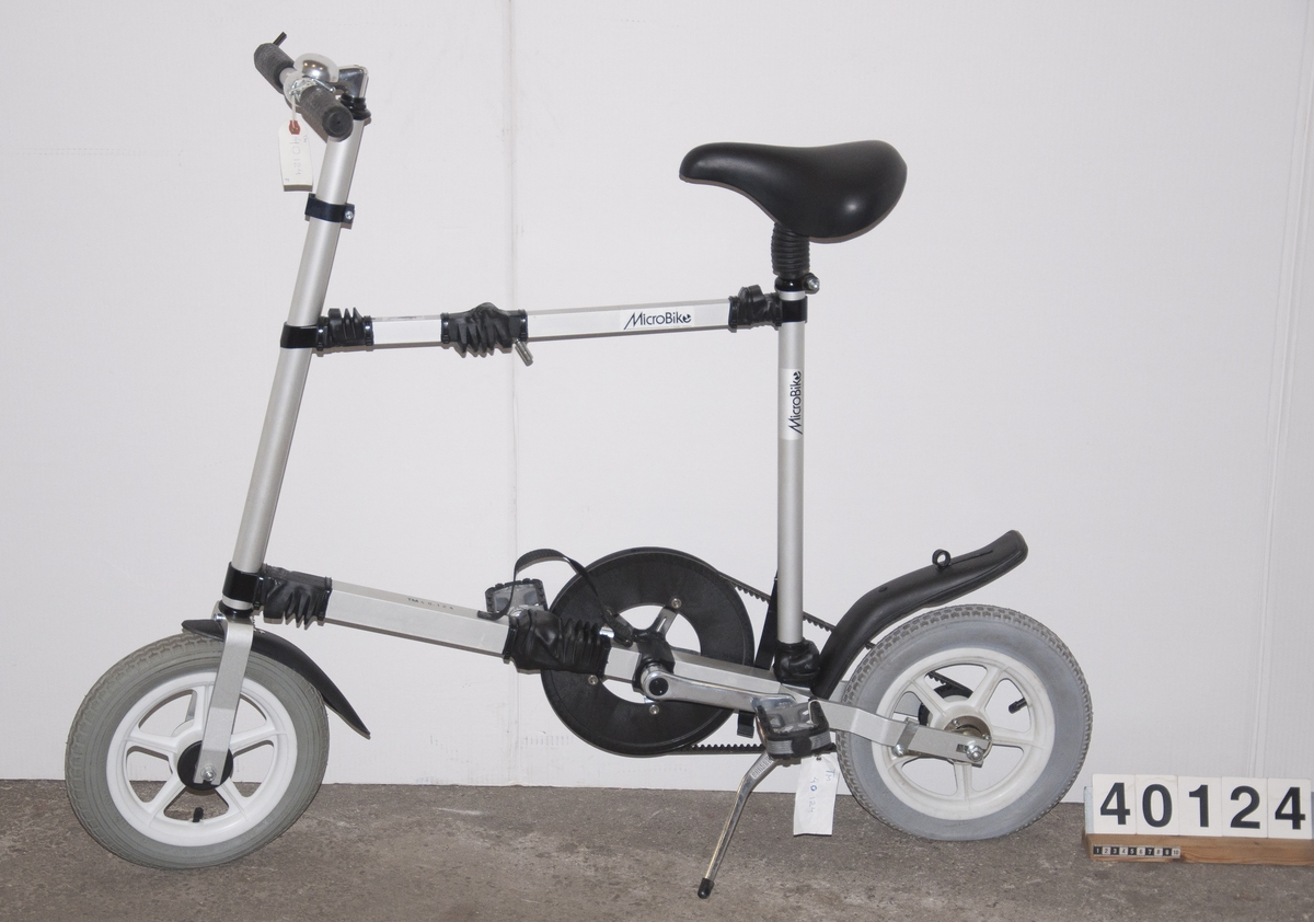 Cykel, hopfällbar låghjuling av plast, gummi och aluminium. Drivs av kevlarförstärkt kuggrem. Hjulbas: 90 cm. Tillbehör: Fast insexnyckel: 6 mm.