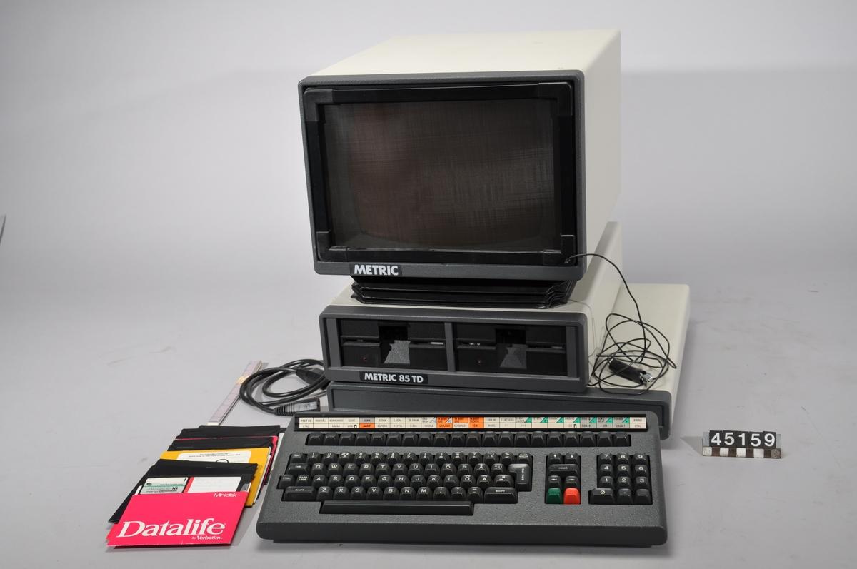 """Bildskärm och tangentbord samt enhet med dubbla floppydiskspelare och dator.  Tillhörande bälg för justering av bildskärmens vinkel, antistatfilter med jordningssladd för bildskärm, alfanumeriskt tangentbord med tolklist för snabbkommandon samt 5 1/4"""" floppydisk med Basic, drivrutiner, Text (ordbehandlingsprogram).  Metric 85 TD har 62 Kb i internminnet och som standard två flexskivor som sekundärminne. Flexskivorna rymmer vardera antingen 160 eller 315 Kb."""