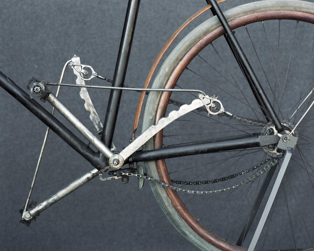 """Tvåhjulig velociped, med vertikaltrampning. Träfälgar och träskärmar, originaldäck, troligen nya pedaler. Fabriksnummer (under velocipeden på sadelstolpsstödet). Skylt: """"Akt. Palmcrantz & Co, Stockholm"""", """"Svea"""". Framhjulsnavet är märkt: """"The Leader""""."""