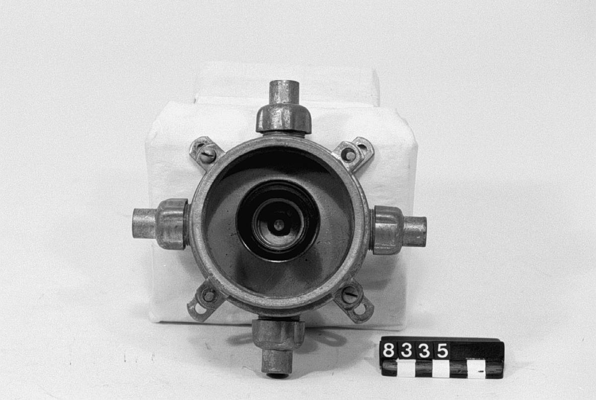 """Kors-dosa, med hållare för glödlampa. Enligt Sieverts system """"SS"""" för elektrisk installation med gummiblyledning i fuktiga och eldfarliga lokaler. Lamphållaren med fast skydd för att hindra beröring med strömförande delar."""