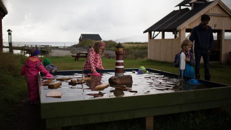 Lekebassenget er populært. Til høyre ligger bålhuset, der  man kan spise under tak og grille hvis man vil. Foto: Langfjurru Foto.