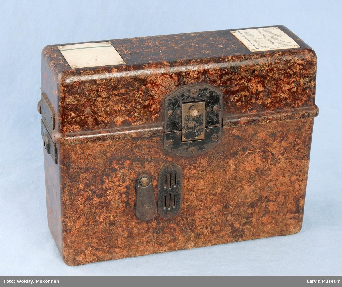Form: Rektangulær boks hvor alt til telefonen finnes oppi lokket er hengslet på den ene siden og kan vippes opp.