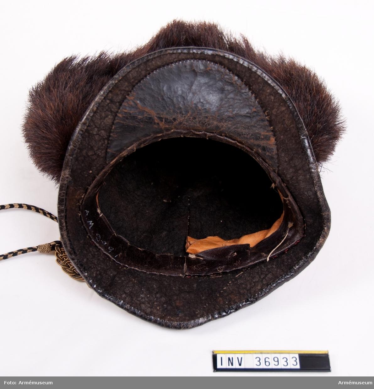 Grupp C I. Ur uniform för officer vid Västgöta linjedragonregemente; 1806-11. Består av mössa, vapenplåt, kordong, jacka, ridbyxor, halsduk, kartusch, rem, sabelkoppel, handrem, taska, remmar, epåletter, skärp, kraghandskar, stövlar, sporrar. Mössan är omstockad från en kask.