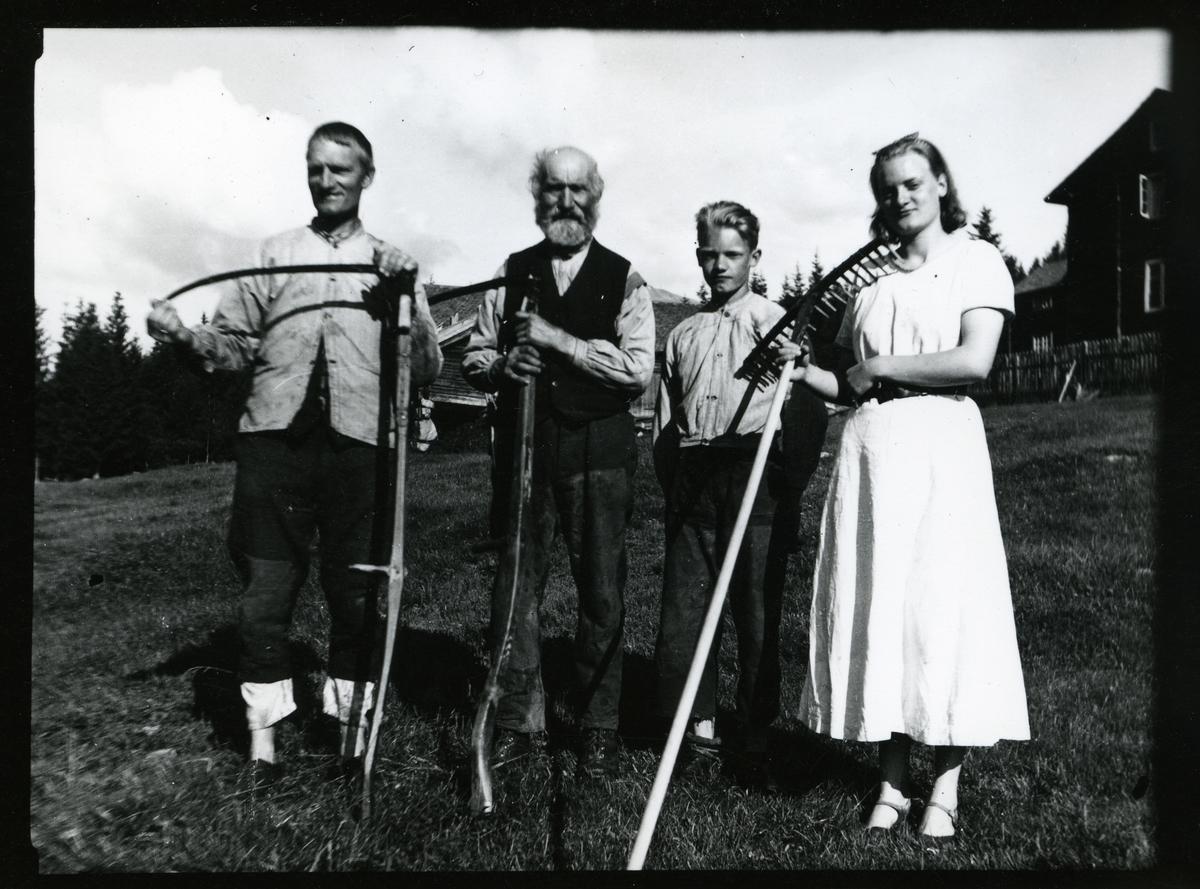 Ei kvinne, ein gutt og to menn står oppstilt på eit jorde. Husa i bakgrunnen. Kvinna held ei rive og mennene har ljåar.