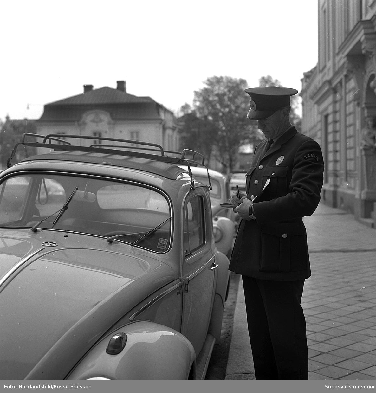 En felparkerad folkvagnsbubbla på Nytorget får en P-bot av en trafikvakt.