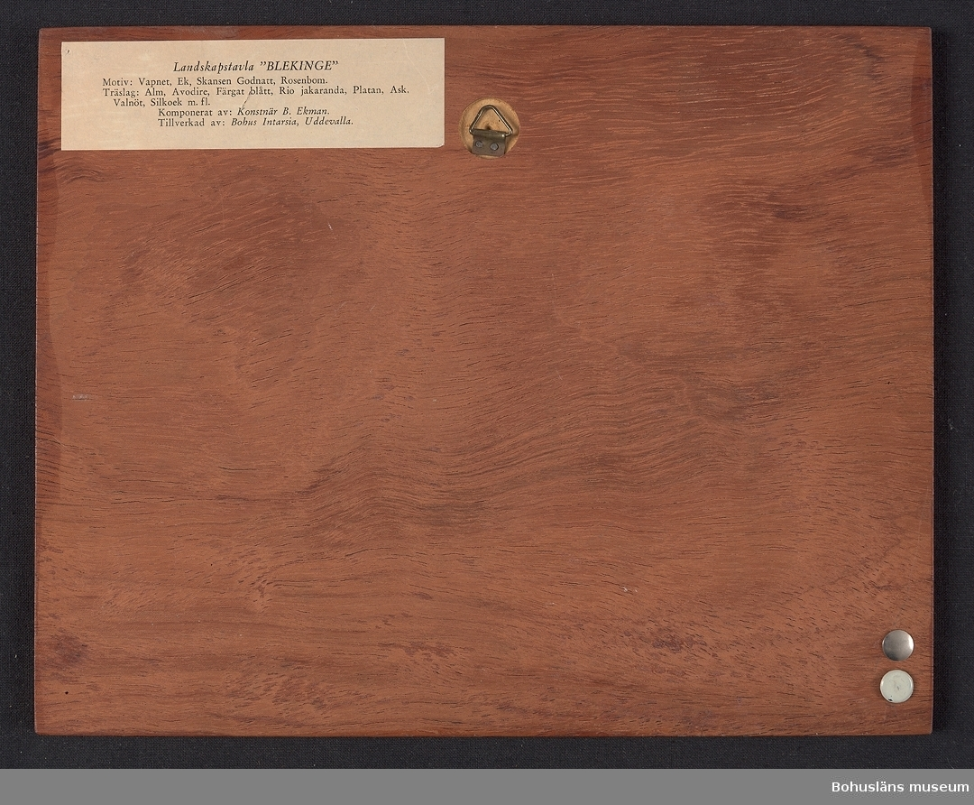 """Landskapstavla med namnet BLEKINGE med landskapsvapnet, en ek med tre kronor uppträdda på stammen och ikoniska motiv typiska för landskapet inlagda i intarsiateknik av fanér i olika ljusa och mörka träslag. Några mindre bitar är infärgade i grönt och rött. Lackad.  Motiven avbildar en ekkvist med löv och ekollon, befästningstornet Godnatt och Gubben Rosenbom.  Intarsian är skuren så att träets naturliga mönster skickligt medverkar till och understryker motivens former och volymer.  Beskrivande etikett av papper på baksidan med texten: Landskapstavla """"BLEKINGE"""" Motiv: Vapnet, Ek, Skansen Godnatt, Rosenbom. Träslag: Alm, Avodire, Färgat Blått, Rio jakaranda, Platan, Ask, Valnöt, Silkock, m. fl.. Komponerat av: Konstnär B. Ekman. Tillverkad av: Bohus Intarsia, Uddevalla. På baksidan en upphängning."""
