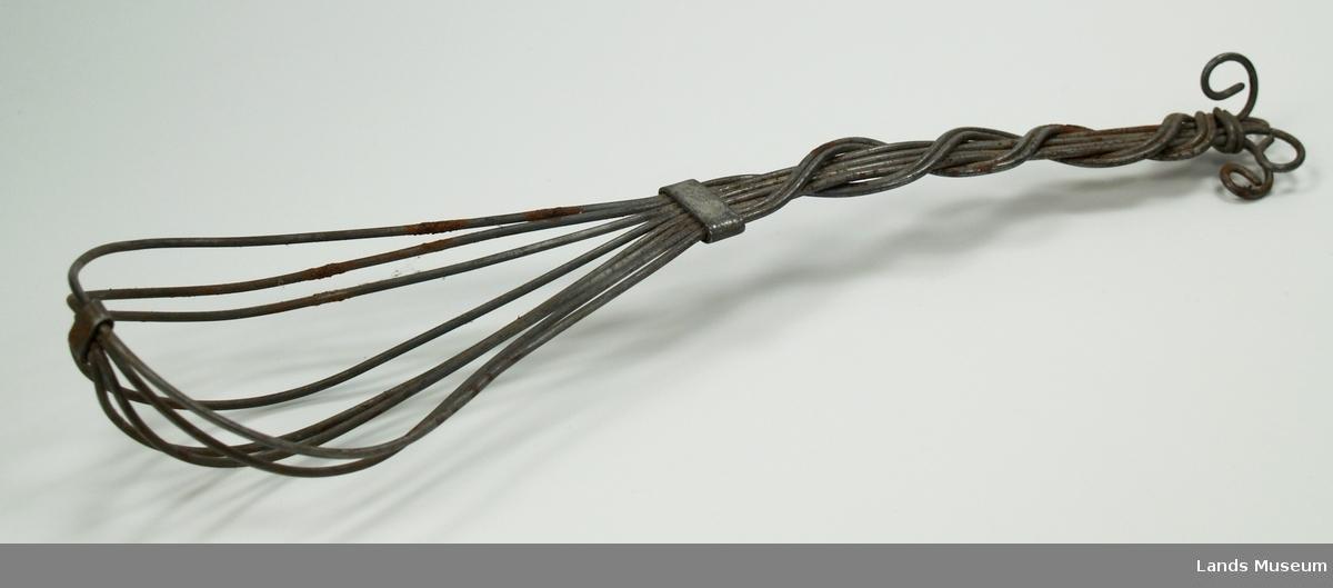 Visp i strengarbeid. Laget av 4 tråder. Tvunnet mønster på skaft. Festet med metallstykker.