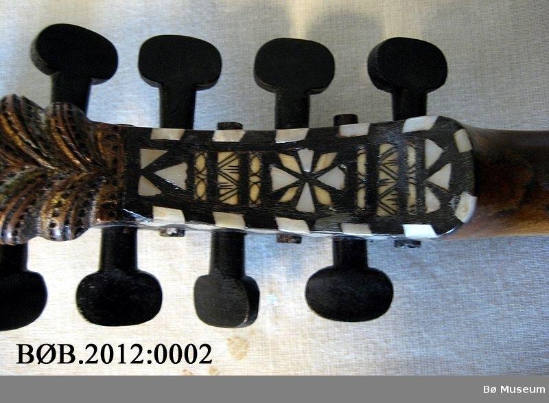 Lokk, ytst langs kanten: Rand med perlemorbetar og svartmåla felt. Innanfor rand med trekantar i tusj (?) Lokket: Akantus i midtfeltet, dekorert med raudmåling. Botn: Dekor langs kantene likt lokket, bortsett fra at trekantene manglar. Perlemor lagt inn i øvre og nedre ende av botn, akantusfelt i midten. Sargene har blomemotiv i tusj, raudfarga som i lokket.