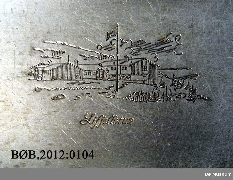 Bilde av Lifjellstua er trykt inn i fatet, midt på. Bord rundt kanten av fatet.
