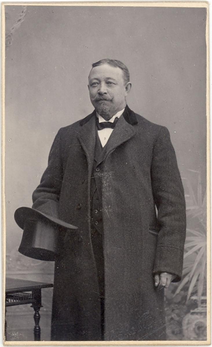 Mann m. frakk og flosshatt ståande i atelier. Mannen er ein handelsreisande til Åheim landhandel i Bø  ved namn Bye.
