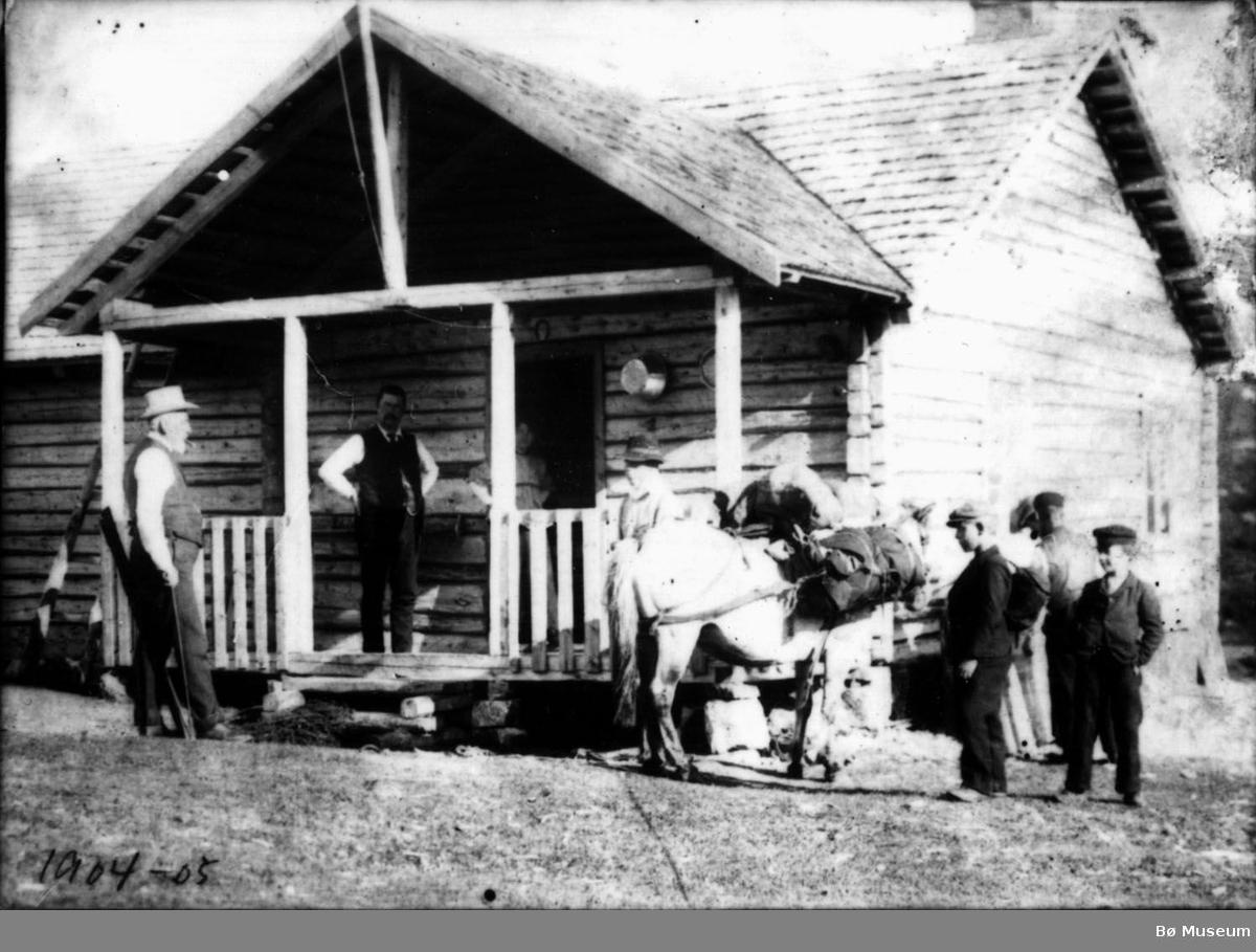 Tømmerhytte med folk og dyr utanfor, Daae-hytta på Hollane