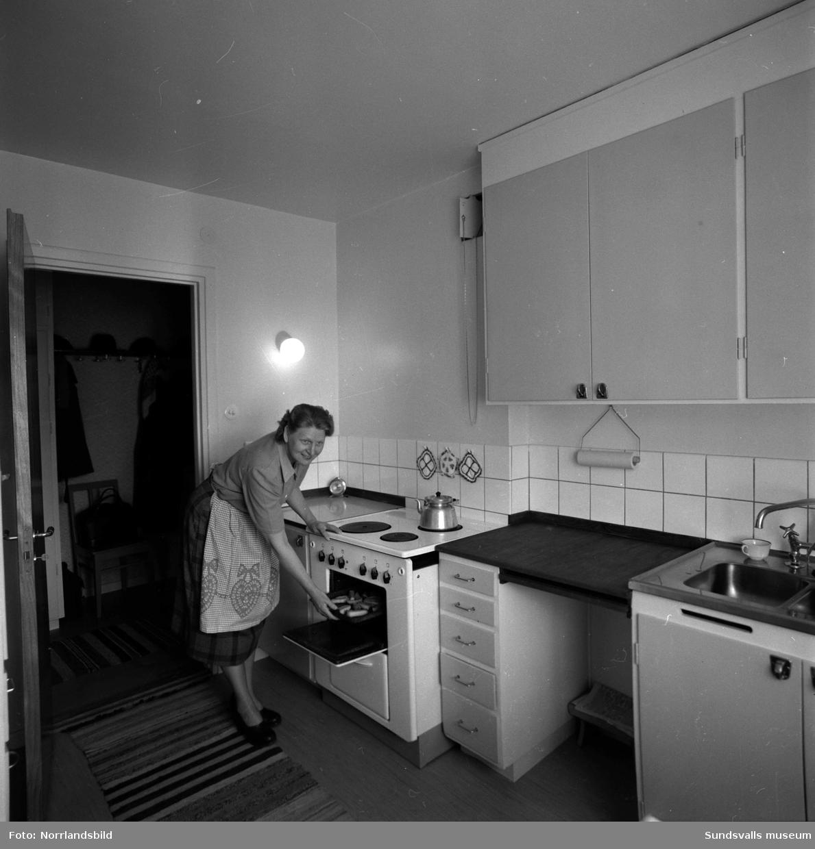 Reportage om bostäder vid Sunds bruk. Hyreslänga vid Finstavägen 31-45. Exteriörbild samt interiör i ett kök med en kvinna vid spisen.