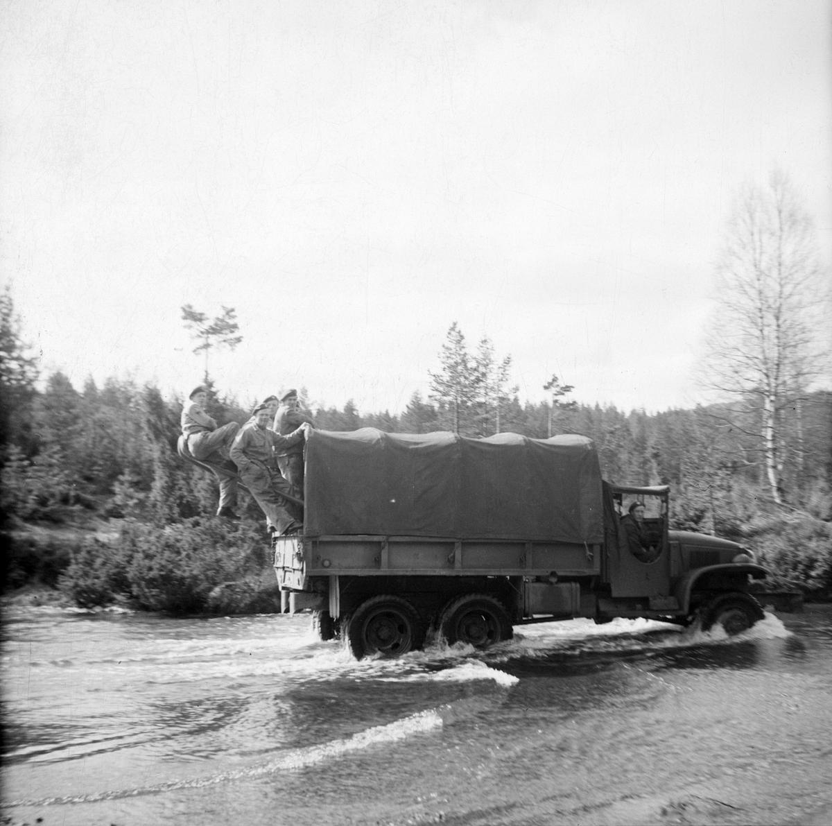 Soldater henger bakpå en militær lastebil.
