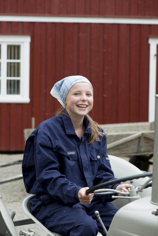 Jente i arbeidsklær på gråtass-traktor