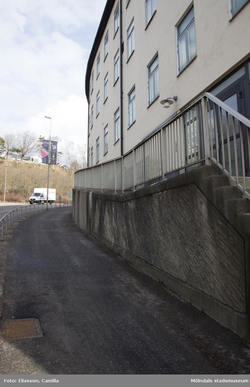 """Kvarnbygatan """"Kråkan"""" i östlig riktning. Till vänster låg tidigare flera byggnader. Samtliga har rivits och gatan har planats ut. Till höger ligger f.d Samuelssons strumpfabrik """"Strumpan"""" på Kvarnbygatan 10. Byggnaden har även adresserna nr 12 (Mölndals stadsmuseum och Forscaféet) samt nr 14. Innanför huset rinner Mölndalsfallen (ej i bild) och ansluter till Mölndalsån."""
