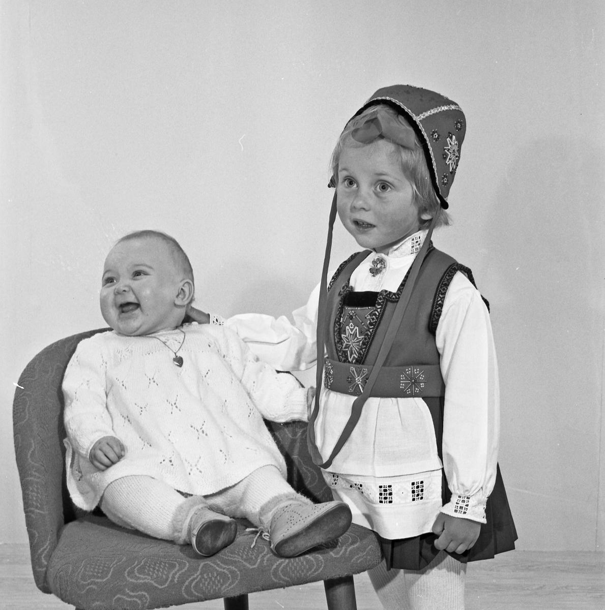 Gruppebilde, famile, ung jente i bunad, lite barn samt foreldre - bestiller Svein Saltvedt
