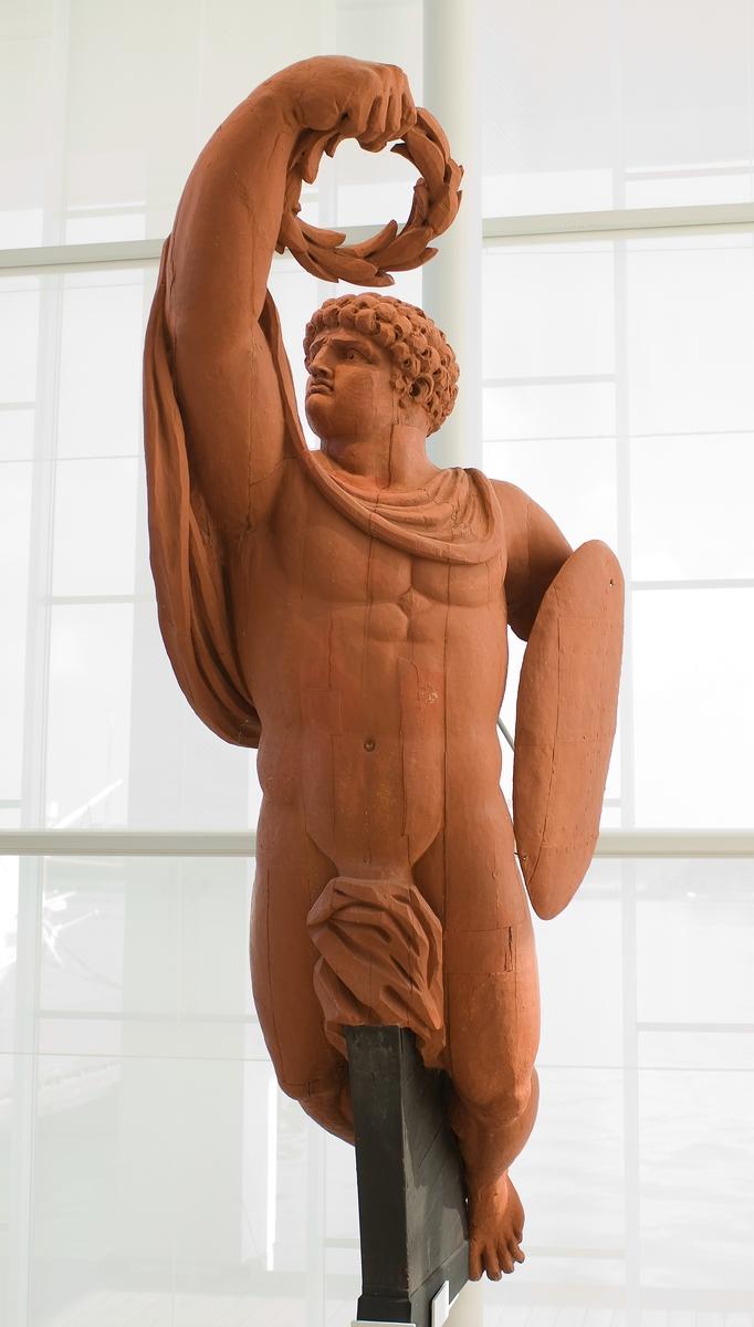 Galjonsbild tillhörande linjeskeppet Äran. Naken manlig helfigur med högervridet huvud och höger arm sträckt framåt-uppåt hållande en lagerkrans. Över vänster arm sitter en mindre oval sköld. Drapering kring hals över höger överarm och mellan benen. Förg: Röd (ursprung engelskr rött)