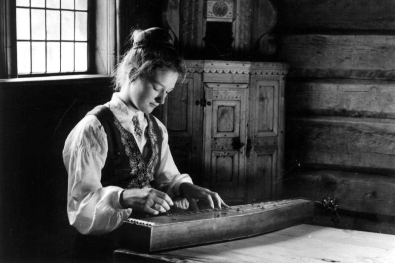 En unge jente i Valdresbunad spiller langeleik i Hålistua fra Vang. 1962,