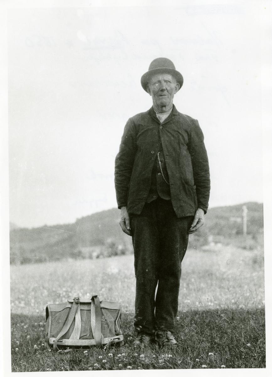 Portrett i helfigur av en mann iført hatt og mørk dress. På bakken ligger en ryggsekk.