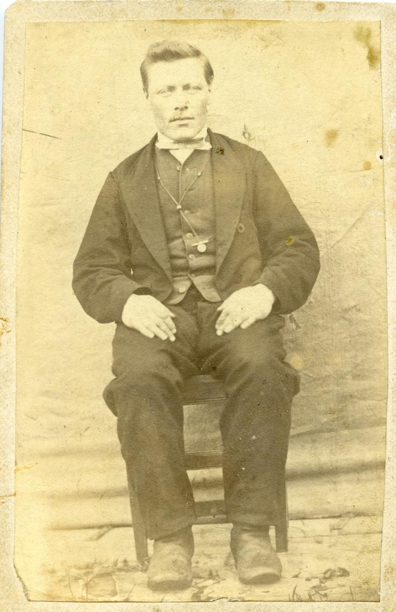 Portrett av en mann sittende på en stol foran et lerret. Mannen er iført dress med vest og skjorte.