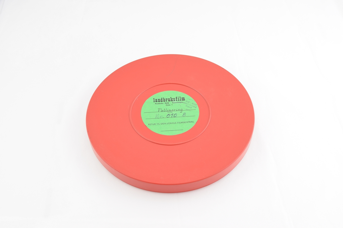 Filmrull i eske. Film på blå plastikkspole. Rødt rundt etui med rund grønn etikett.