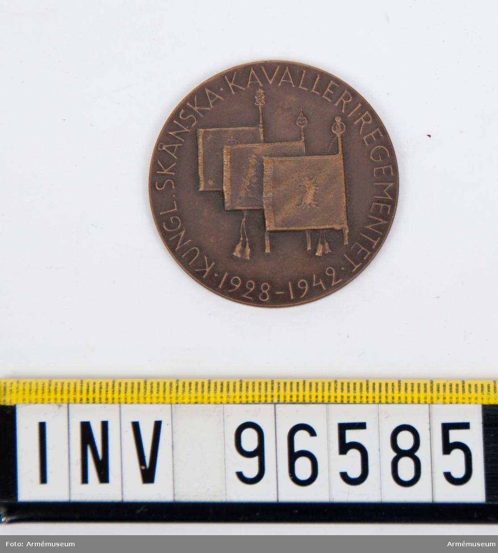 Medalj i brons för Skånska kavalleriregementet. Stans 14513, härdad 1942-10-21. Medalj, storlek 40 mm diameter, åtsida med tre standar inom omskrift KUNGL. SKÅNSKA KAVALLERIREGEMENTET 1928 1942, enligt modell av skulptören Karl Hultström.