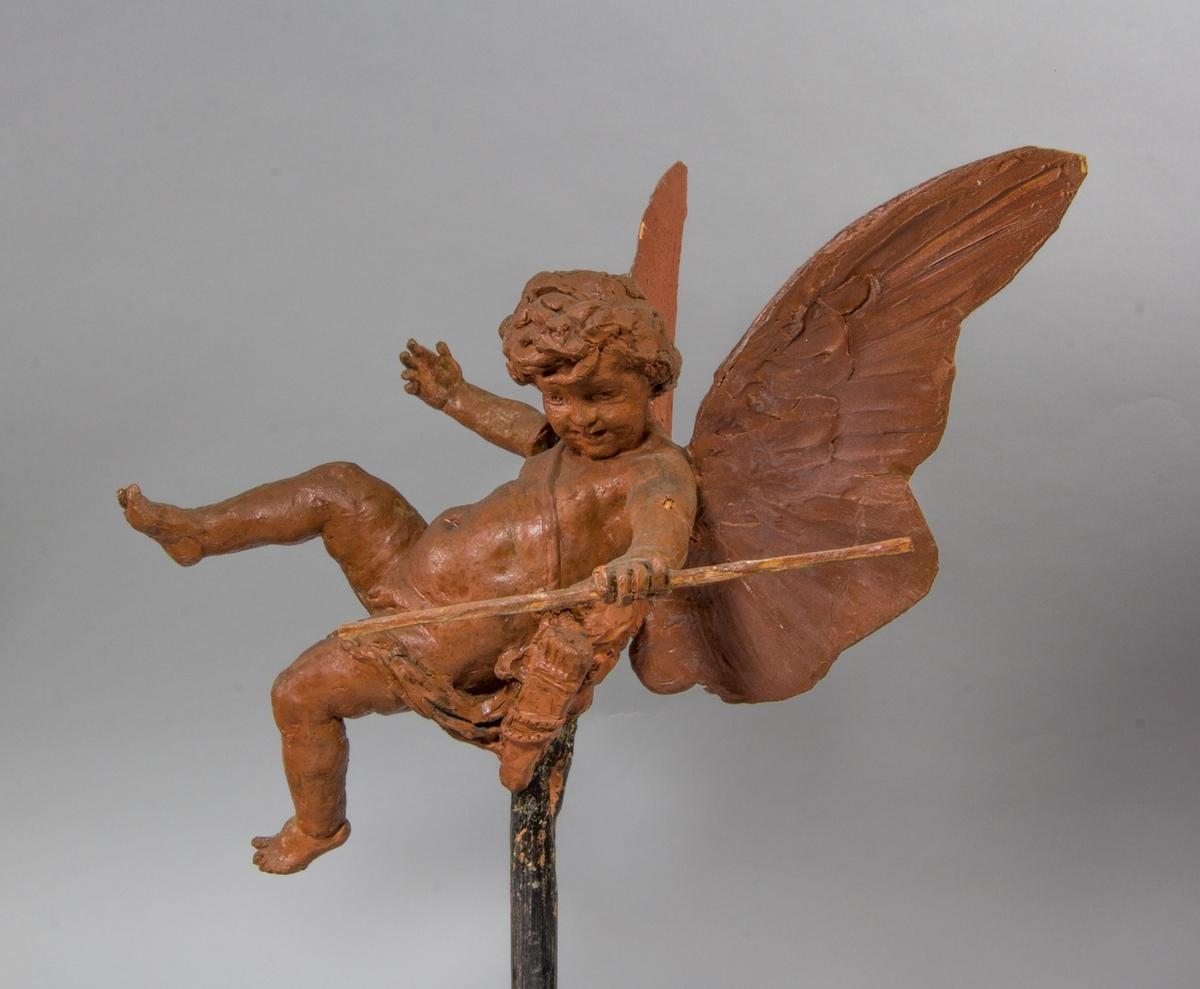 Amorin i helfigur, flygande, och med pilbåge i ena handen och pilkorger på sidan.