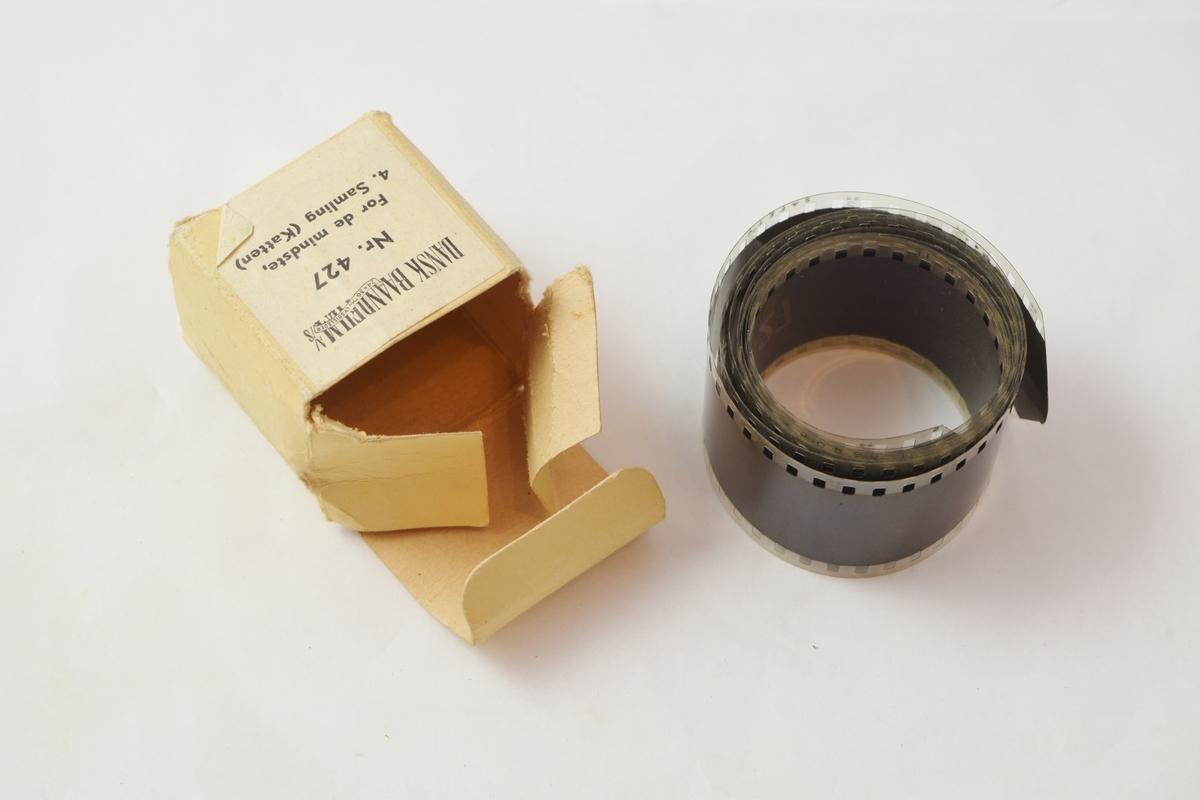 Filmrull i eske. Film uten spole. Kubeformet papireske hvor lokket henger fast i bunnen.