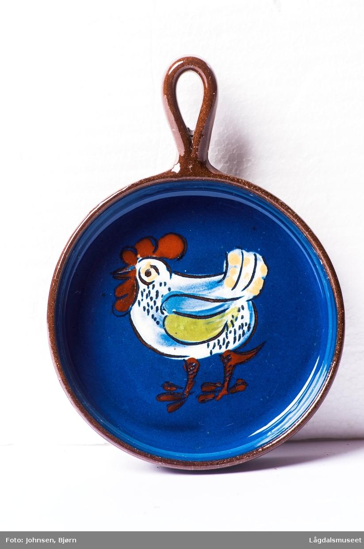Pannen er dekorert med et motiv av en høne i begitning.