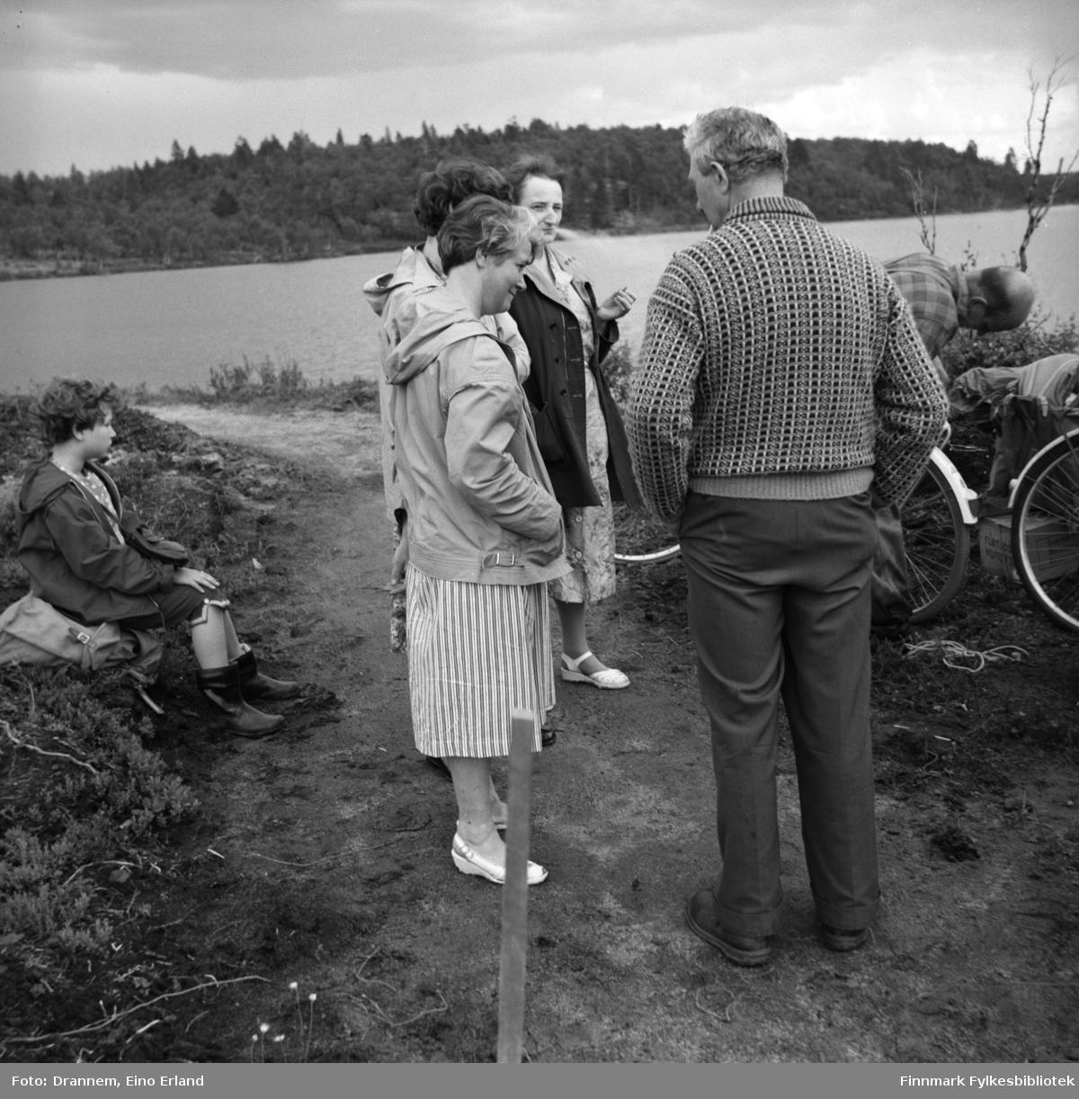 Fem personer ved bredden av et vann/en innsjø. Fra venstre sitter Turid Karikoski, foran henne står tre damer. Sonja Lappalainen nærmest kamera og to ukjente delvis skjult bak henne. Søren Gabrielsen med ryggen til og bøyd over en sykkel står Uuno Lappalainen. Bildet kan være tatt Jääjärvi i Finland.