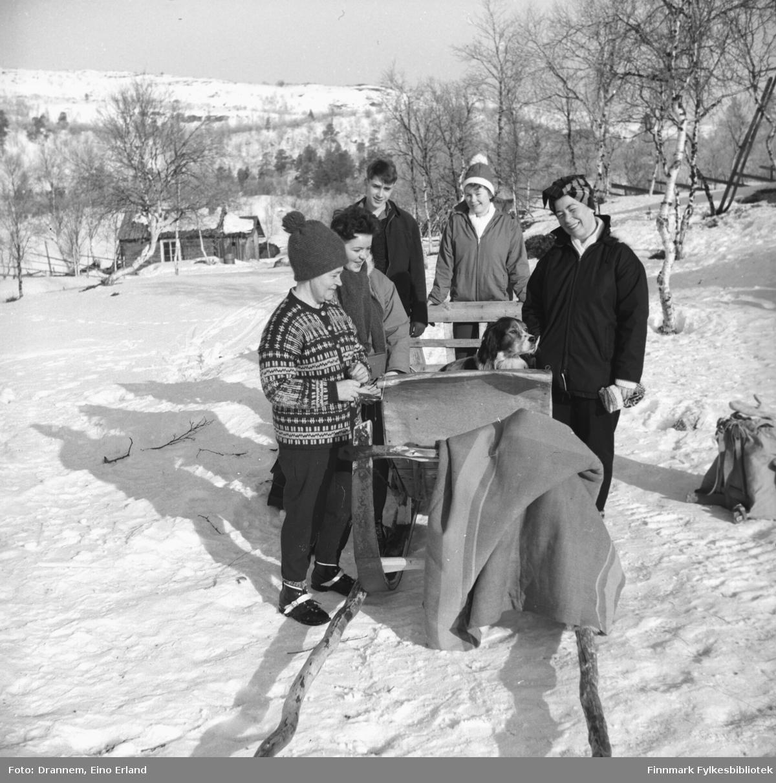 Fem personer står rundt en slede med hunden Rexi oppi. De er fra venstre: Sonja Lappalainen, Maija - etternavn ukjent- , Gunnar Gabrielsen, Turid Karikoski og Jenny Drannem.