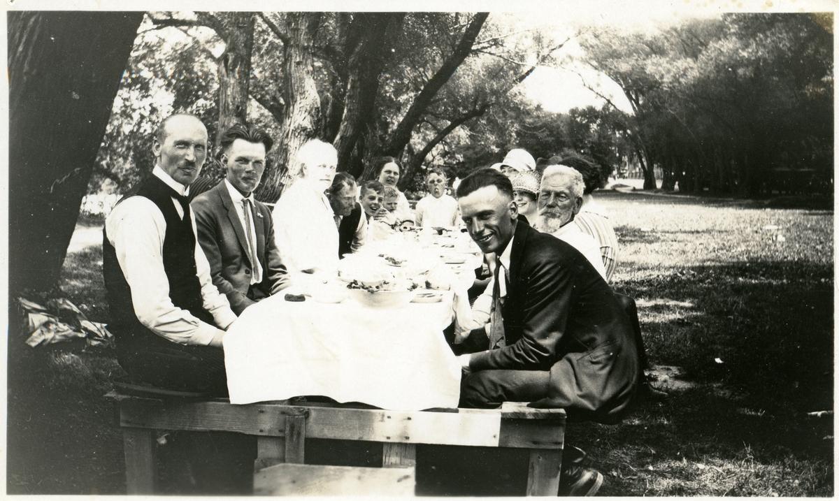 Barn og voksne rundt et dekket bord i en bypark i Madison, Wise. Olaus Islandsmoen til venstre. Peder Hansen Islandsmoen og Gurine er også på bildet.