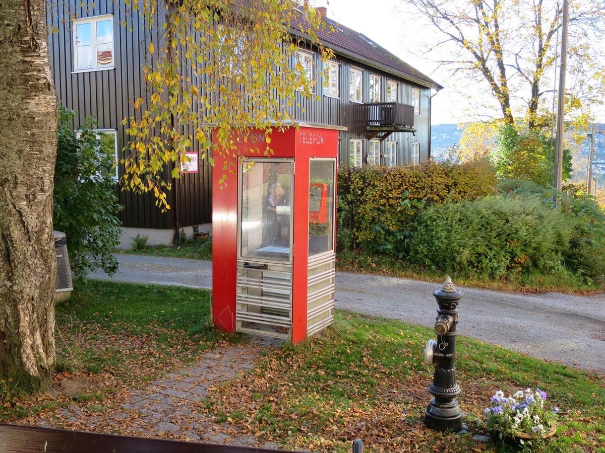 Denne telefonkiosken står på torvet i Øvrebyen i Kongsvinger, og er en av de 100 vernede telefonkioskene i Norge. De røde telefonkioskene ble laget av hovedverkstedet til Telenor (Telegrafverket, Televerket). Målene er så å si uforandret.  Vi har dessverre ikke hatt kapasitet til å gjøre grundige mål av hver enkelt kiosk som er vernet.  Blant annet er vekten og høyden på døra endret fra tegningene til hovedverkstedet fra 1933. Målene fra 1933 var: Høyde 2500 mm + sokkel på ca 70 mm Grunnflate 1000x1000 mm. Vekt 850 kg. Mange av oss har minner knyttet til den lille røde bygningen. Historien om telefonkiosken er på mange måter historien om oss.  Derfor ble 100 av de røde telefonkioskene rundt om i landet vernet i 1997. Dette er en av dem.