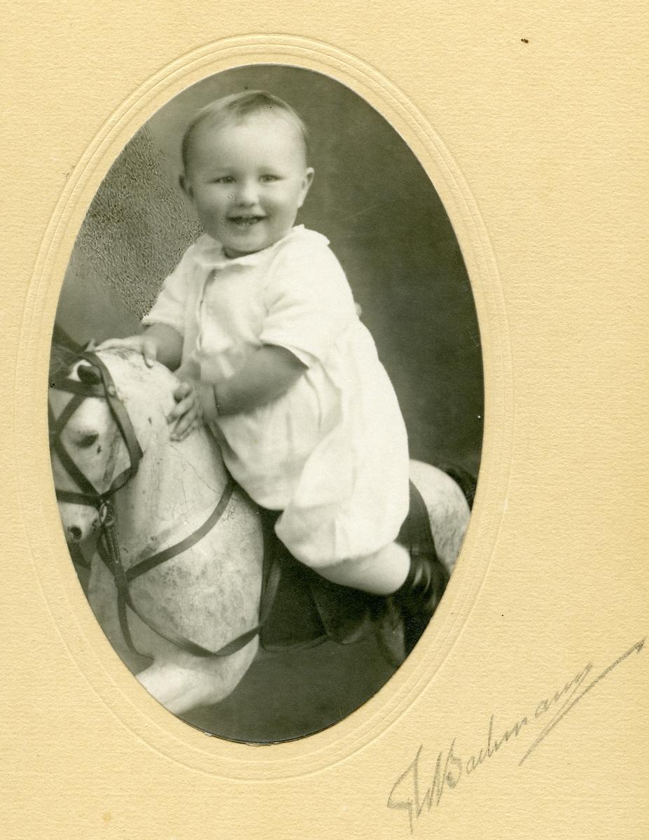 Barnefoto av Per Islandsmoen i 2-årsalderen sittende på en gyngehest.