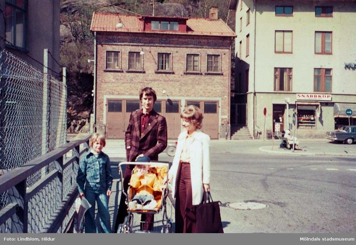 En kvinna, en man och två barn, det ena i barnvagn, står på Forsebron i Mölndal, 1970-tal. I bakgrunden till vänster ses del av gaveln till huset Kvarnbygatan 4. I mitten ses Kvarnbygatan 41, tidigare brandstation och garage för polisbilar, numera Mölndals målarskola. Till höger ses del av huset Kvarnbygatan 43, tidigare Mölndals stadshus, sedermera musikskola.  För mer information om bilden se under tilläggsinformation.