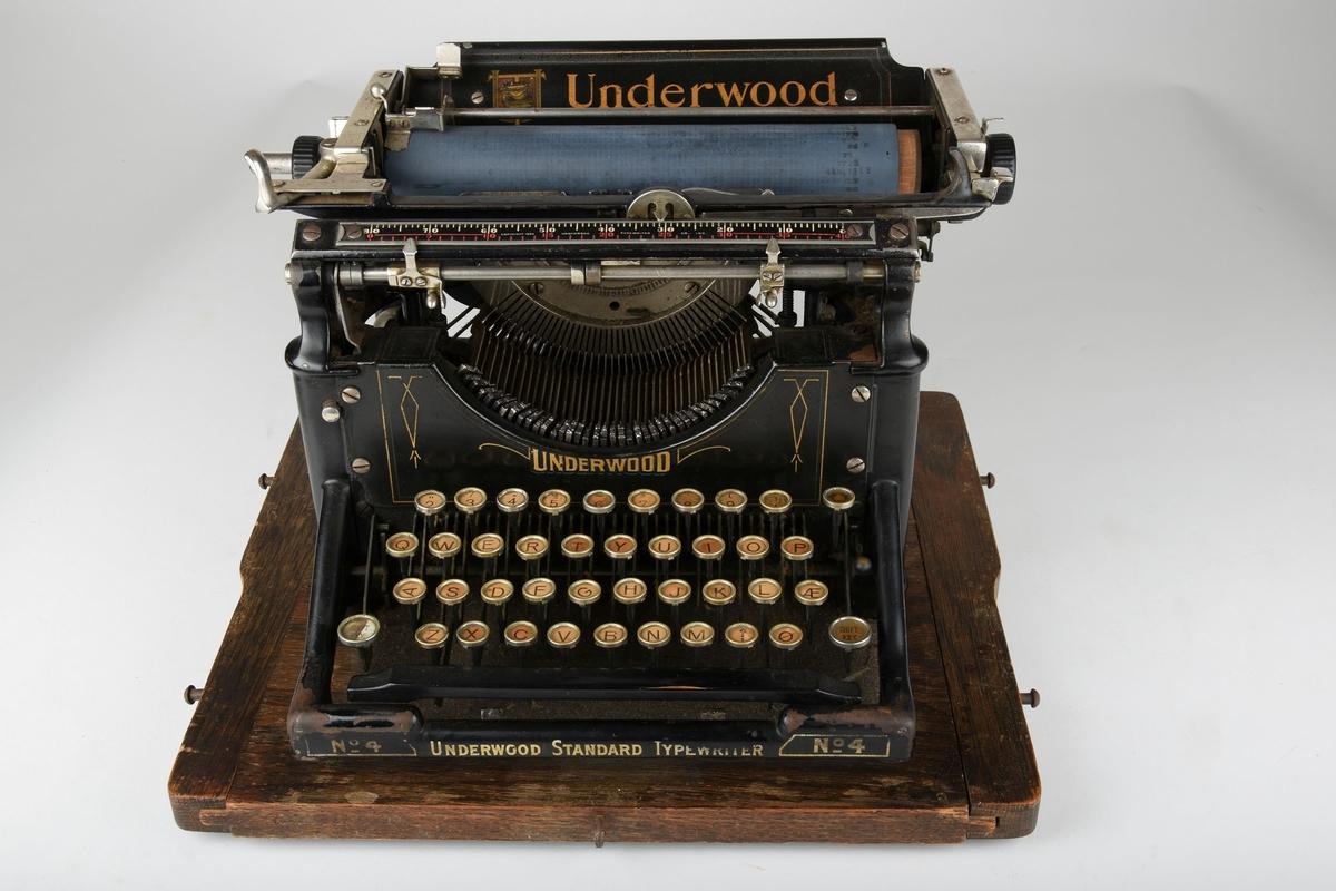 Skrivemaskin med deksel. Dekselet har håndtak i toppen.   Skrivemaskinen er kraftig og står på en treplate som dekslet kan festes til.