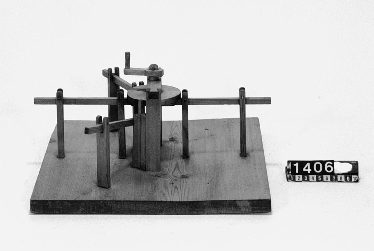 Modell ur Polhems mekaniska alfabet. Den horisontella cirkelskivan är på undersidan försedd med ett spår i vilket det löper tappar, som är fästade på armarna. När skivan roterar får armarna en fram- och återgående rörelse.