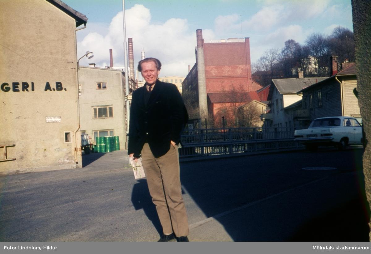 Konstnär Lars Börjesson, kusinbarn till Karin Gren som ägde Rasmussons skoaffär, fotograferad vid Forsebron i Mölndal, 1960-tal. I bakgrunden till vänster ses del av gaveln till huset Kvarnbygatan 6, byggnad tillhörande SOAB. I mitten ses Stora Götafors och till höger Götaforsliden 1-5.  För mer information om bilden se under tilläggsinformation.