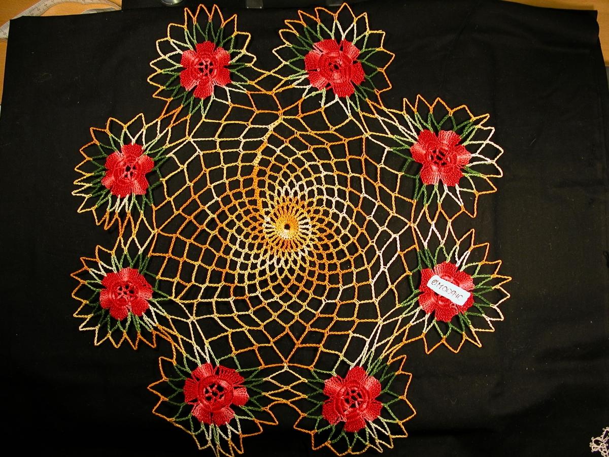 Fiskegarnsmønster i sirkel, hekla i flammegarn, gul. Rundt kanten er det 8 roser, der rosa er raud og ein bladkant er grøn. Desse er også i flammegarn. Gul kant rundt kvart rose-emne.
