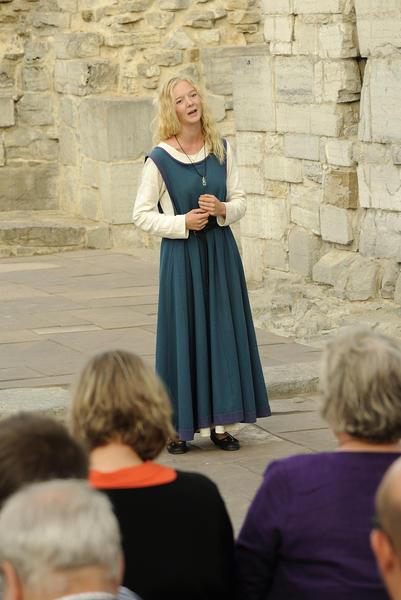 Lyshåret, ung jente iført hvit, langermet linkjole under og en blågrønn overkjole i ull står og synger for publikum i vernebygget over domkirkeruinen.. Foto/Photo